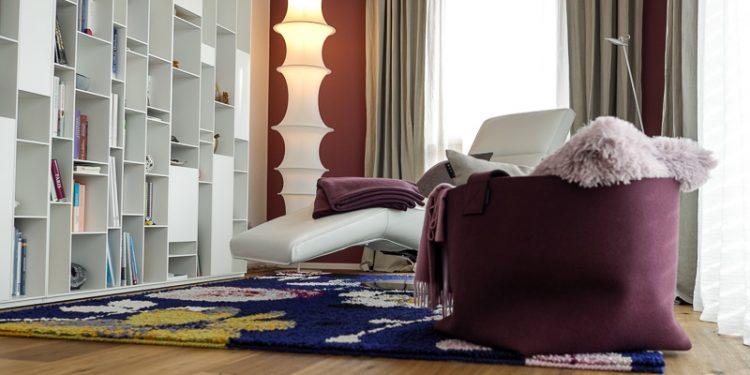 Leseecke mit weißem Regal, weißer Liege und rotem Sessel